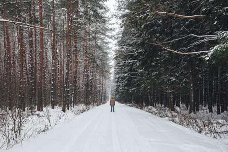 Молодой человек стоит на зимней лесной дороге, покрытой снегом Фото со стока - 91700936