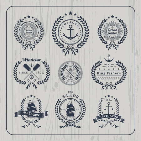 Vintage nautical wreath labels logo set and design element on light wood background. Vectores