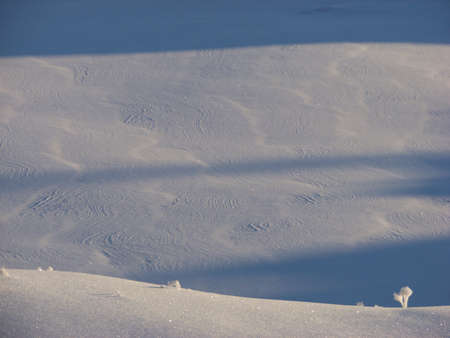 wind down: Looking down to the bottom of a hill to a wind blown snow patterns
