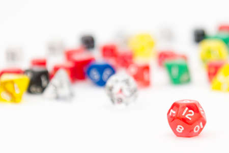 boardgames: Image of 12-sided RPG dice with other dice on background. RPGs and boardgames use dices with different amount of sides like d4, d6, d8, d10, d12 and d20.