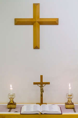 blessed trinity: Small and simple christian altar with candles, bible, Jesus cross and big wooden cross on the wall.