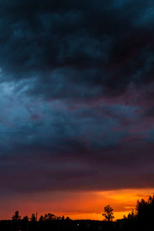 poster cloudscape of setting sun and dark stormy clouds with vivid colors.