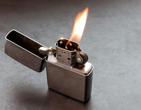 Encendedor de metal de plata en fondo oscuro con la llama.