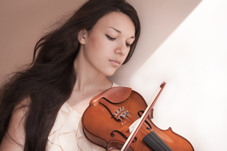 Pretty young female playing the violin, soft focus.  photo