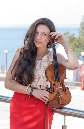 Pretty young woman in red dress with violin, soft focus  photo