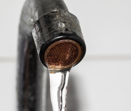 Rusty metal tap with water drop