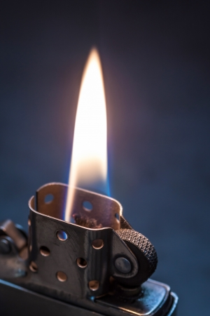 Metal lighter on black background with flame   photo