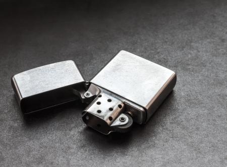 Silver metal lighter on black background.