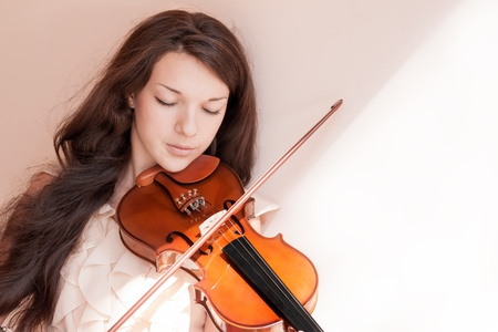 Portrait of a pretty young female playing the violin, soft focus.