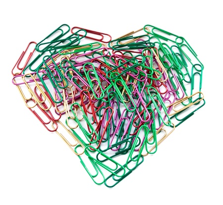 Multi color paper clips arranged in heart shape isolated on white   photo