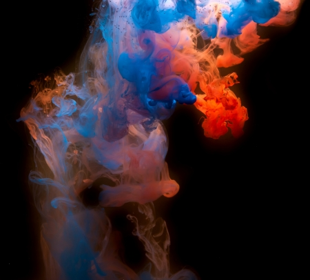 Red and blue Ink in water on a black background.