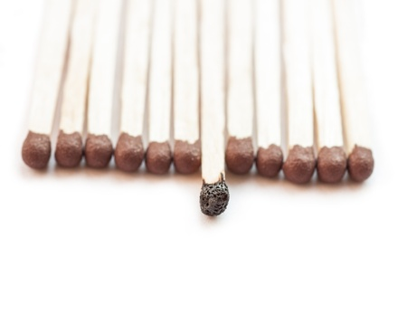 A row of matches with one burnt. Stock Photo - 18850309