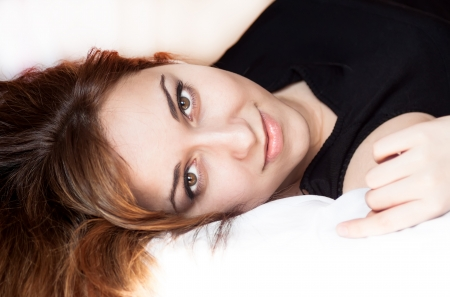 Closeup portrait of a beautiful young lady lying on the bed. Stock Photo - 20134491
