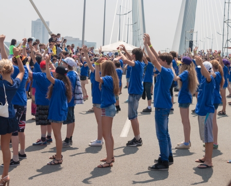 danced: VLADIVOSTOK, RUSSIA - JULY 7: dance Flash mob on the Golden Bridge. It was attended by hundred people who danced on   the Golden Bridge on July 7, 2013 in Vladivostok, Russia.