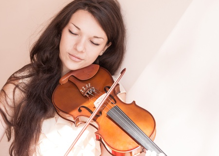 Portrait of a pretty young female playing the violin, soft focus  photo