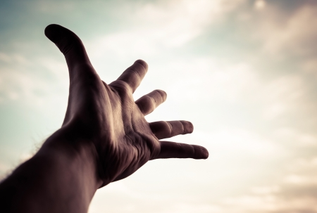 Hand of a man reaching to towards sky  Color toned image  Stock Photo