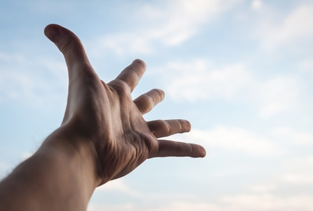 Hand of a man reaching to towards sky   photo