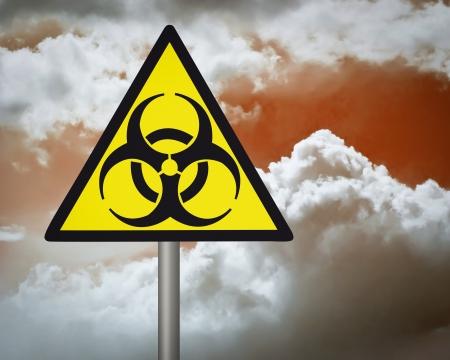 biological waste:    Yellow biohazard warning sign on against dark cloudy sky