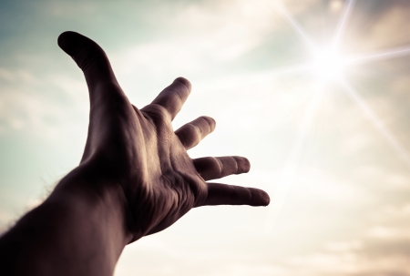 Hand of a man reaching to towards sky  Color toned image   Imagens