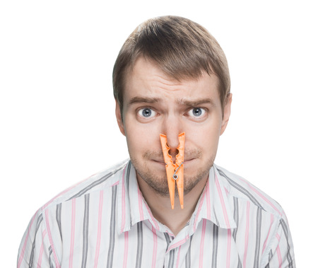 Portrait of caucasian man with orange clothespin on his nose - bad smell concept photography  Banque d'images