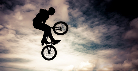 Silhouette of a man doing an jump with a bmx bike  Color toned image