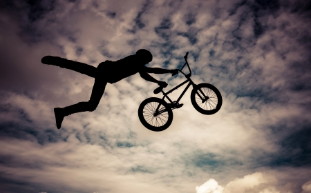 Silhouette of a man doing an jump with a bmx bike  Color toned image  Stock Photo