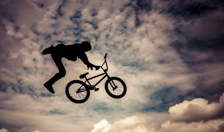 bmx bike:   Silhouette of a man doing an jump with a bmx bike  Color toned image  Stock Photo