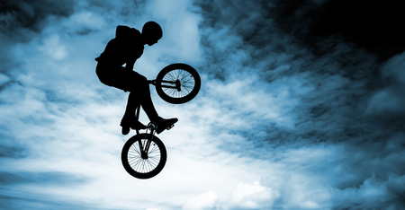 Silhouette of a man doing an jump with a bmx bike over blue sky background  photo