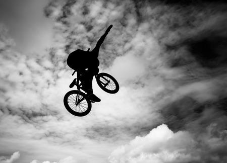 bmx bike:  Silhouette of a man doing an jump with a bmx bike