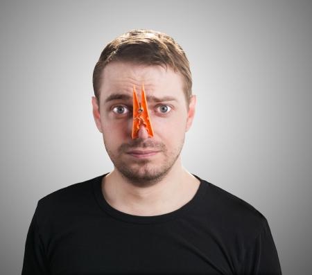 Portrait der kaukasischen Mann mit orange Wäscheklammer auf der Nase - schlechter Geruch Konzept Fotografie Standard-Bild - 23914026
