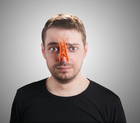 Portrait of caucasian man with orange clothespin on his nose - bad smell concept photography   photo