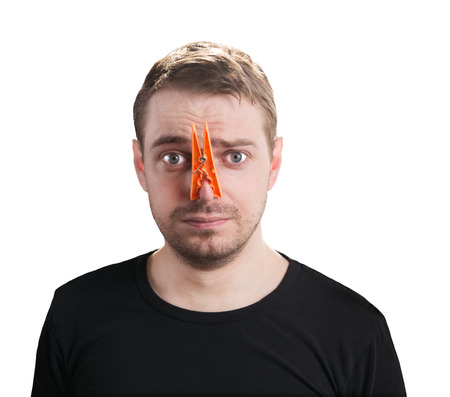 Portrait of caucasian man with orange clothespin on his nose - bad smell concept photography