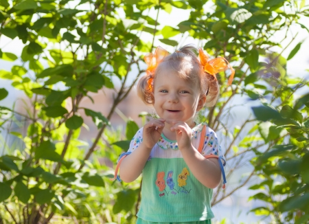 Portrait of smiling happy baby girl on natural bokeh  photo