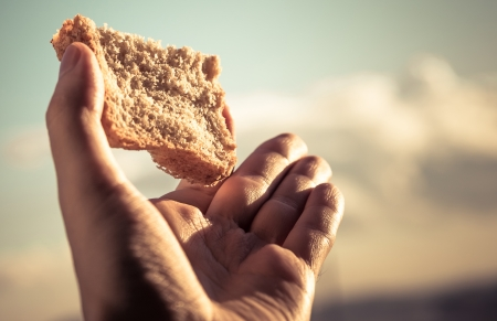 Hand hold a slice of bread over sky background  Color toned image