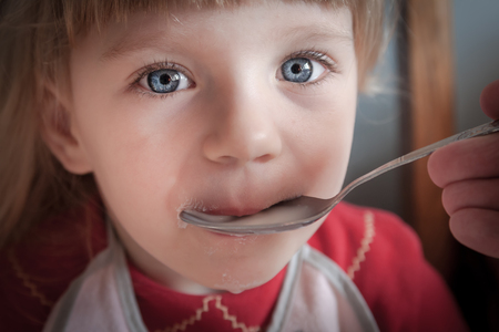 Portrait of blue eyed baby girl being fed by hand  photo