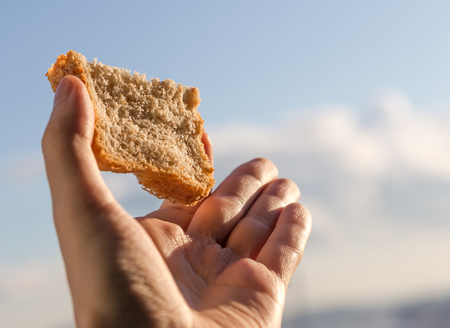 dire:   Hand hold a slice of bread over sky background