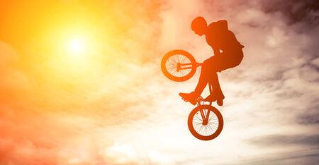 air jump:   Silhouette of a man doing an jump with a bmx bike against sunshine sky