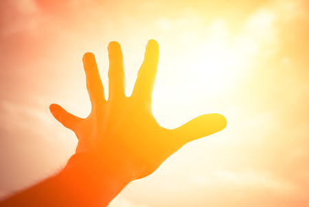 emanation: Hand of a man reaching to towards sunshine sky Stock Photo