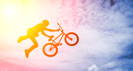 Silhouette of a man doing an jump with a bmx bike against sunshine sky