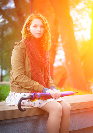 Beautiful redhead girl sits on a bench   photo