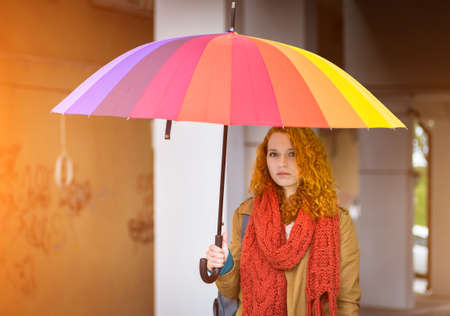 Beautiful redhead girl with umbrella in the sunshine   photo