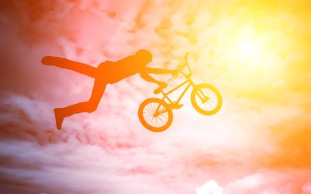 bmx bike: Man doing an jump with a bmx bike against sunshine sky