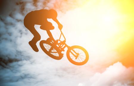 bmx bike:  Silhouette of a man doing an jump with a bmx bike against sunshine sky