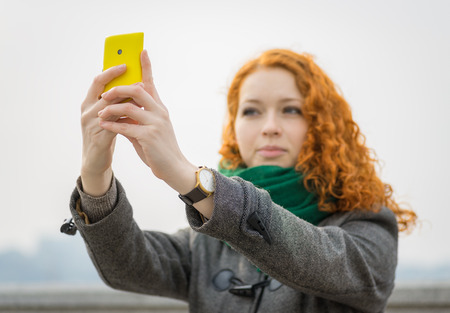 Young redhead girl taking a selfie outdoors