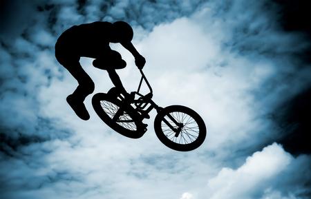 bmx bike:  Silhouette of a man doing an jump with a bmx bike  Stock Photo
