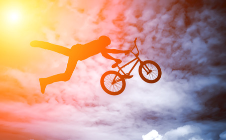 Silhouette of a man doing an jump with a bmx bike against sunshine sky  photo