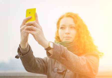 Young redhead girl taking a selfie outdoors on sunny day