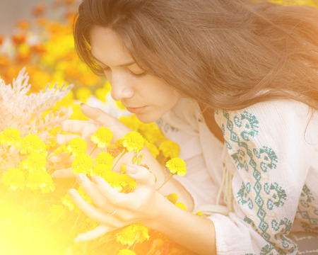 Young girl smelling yellow flowers with the sunshine   photo