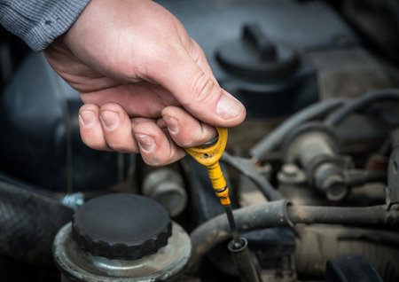 Auto Mechanic checking oil  Selective focus with shallow depth of field