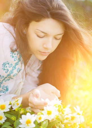 Young beautiful woman smelling yellow flowers in garden with the sunshine   photo